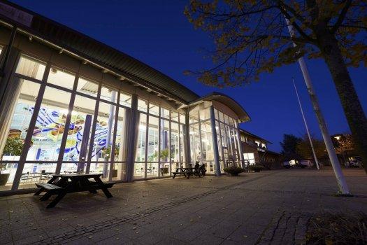 Aften billede af Ikast Svømmecenters hovedindgang fra venstre side.